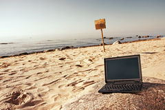 Laptop and sign at beach. Single black laptop and woodens sin in background alone at beach Stock Photos
