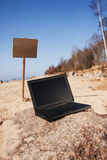 Laptop and sign at beach Royalty Free Stock Photos