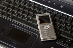 Laptop and silver smart phone Stock Photos