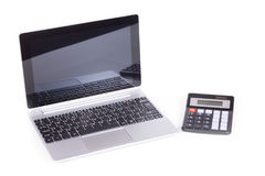 Laptop and simple calculator. Modern laptop with glossy screen and simple small calculator isolated on white background, viewed from high angle Stock Image