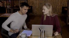 For laptop sits couple and man is surprised looking at monitor of woman. Man`s person experiences emotions from promotion of online stores on computer for stock footage