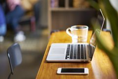 Laptop, smart phone & glass of water on coffee shop table, nobody. Laptop, smart phone & glass of water on indoor table, nobody Royalty Free Stock Image