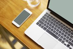 Laptop, smart phone & glass of water on coffee shop table, nobody. Laptop, smart phone & glass of water on indoor table, nobody Royalty Free Stock Photography