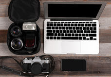 Laptop, smart phone, photo camera and headset on wooden background royalty free stock photos