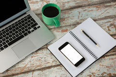 Laptop with smartphone and cup of coffee Stock Images