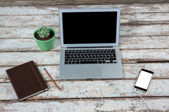 Laptop, smartphone and diary with pot plant Royalty Free Stock Photography