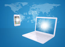 Laptop and smartphone exchange letters. The concept of e-mailing Royalty Free Stock Photography