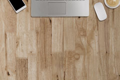 Laptop, smartphone, mouse, coffee cup on wooden desk - working c. Laptop, smartphone, mouse, coffee cup on wooden desk - top view with copy space stock images
