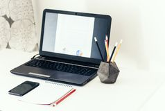 Laptop, smartphone, notebook and pencils in concrete holder on white table in office business background for education learning. Concept stock photography