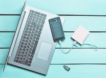 Laptop, smartphone, power bank, USB flash drive on a blue wooden table. Modern digital devices and gadgets. Top view. Laptop, smartphone, power bank, USB flash royalty free stock photos