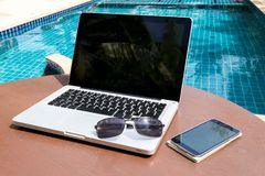 Laptop and smartphone near the pool. Laptop and smartphone with sunglasses on the table near the pool royalty free stock image