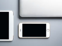 Laptop, smartphone and tablet on gray background. Flat lay and minimalist image of laptop, smartphone and tablet on gray background with copy space Stock Image