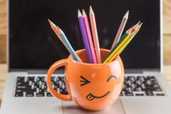 Laptop with smiley wrinkle happy face mug. Royalty Free Stock Images