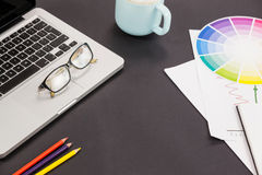 Laptop, spectacles, color pencils, coffee cup and color scheme chart. On grey background Stock Photography