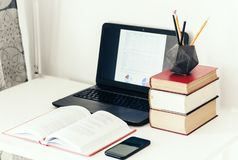 Laptop, stack of books, smartphone, notebook and pencils in concrete holder on white table in office business background for stock images