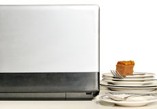 Laptop with stack of dirty plates on working desk Stock Image