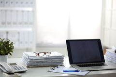 Laptop with stack of folders on table on white stock image
