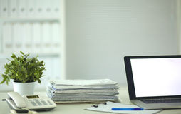 Laptop with stack of folders on table on white Royalty Free Stock Photography