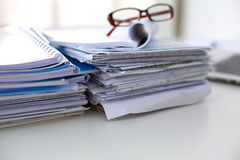 Laptop with stack of folders on table on white Stock Photo