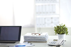 Laptop with stack of folders on table  white background Stock Photos