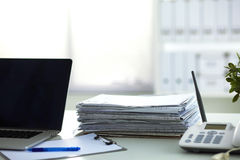 Laptop with stack of folders on table on white background Stock Images