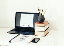 Laptop, stapel boeken, smartphone, notitieboekje en potloden in concrete houder op witte lijst op bureau bedrijfsachtergrond voor royalty-vrije stock foto's