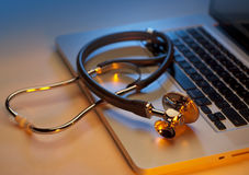 Laptop and stethoscope. Stethoscope on silver laptop computer in blues and oranges Royalty Free Stock Image