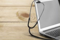Modern laptop and stethoscope on wooden background. Laptop stethoscope top computer background health brown Stock Images