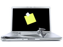 Laptop with sticky note and tool Stock Image