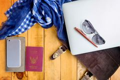 Leather bag notebook and blue check scarf on wood table. Laptop sunglasses passport mobile phone and check scarf on wood table royalty free stock images