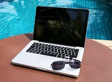 Laptop with sunglasses near the pool. Laptop with sunglasses on the table near the pool stock images