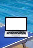Laptop by swimming pool Royalty Free Stock Image