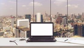 Laptop, szkła i dzienniczek na stole w biurze, fotografia royalty free