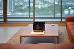 Laptop on table in modern living room with blank screen.  Stock Photo