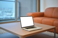 Laptop on table in modern living room with blank screen.  Stock Photography