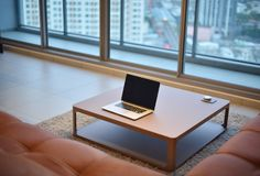 Laptop on table in modern living room with blank screen.  Royalty Free Stock Images