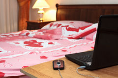 Laptop on table near bed in bedroom Royalty Free Stock Photos