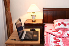 Laptop on table near bed in bedroom Royalty Free Stock Image