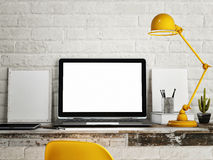 Laptop on table, White brick wall background Royalty Free Stock Photo