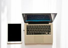 Laptop and tablet with copy space in sunlight. Slightly seeing chart and graph on the computer screen. Flat lay. Laptop and tablet with copy space in sunlight royalty free stock image