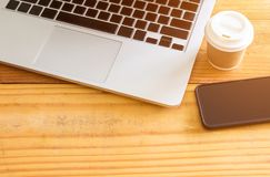 Laptop with tablet and a cup of fresh coffee on wooden table. In coffee shop stock photo
