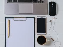 Laptop, tablet with paper, smartphone, pen and earphones on white wooden table. The view from the top. Royalty Free Stock Photo