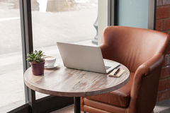 Laptop with tablet, pen and a cup of fresh coffee latte art on w Royalty Free Stock Images