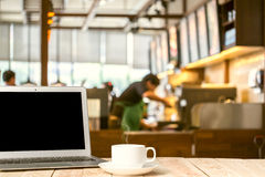 Laptop with tablet, pen and a cup of fresh coffee latte art on w Stock Photos