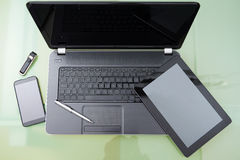 Laptop with tablet and  smart phone on glass table Royalty Free Stock Image