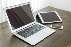 Laptop with tablet and smart phone on table Stock Photo