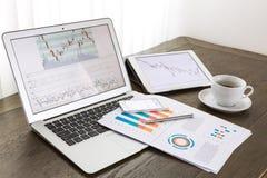 Laptop, Tablette, Smartphone mit Finanzdokumenten Stockbilder