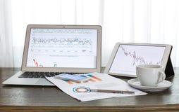 Laptop, Tablette, Smartphone und Kaffeetasse mit Finanz-docume Stockbild