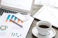 Laptop, Tablette, Smartphone und Kaffeetasse mit Finanz-docume Lizenzfreie Stockfotos