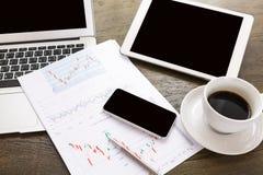 Laptop, Tablette, Smartphone und Kaffeetasse mit Finanz-docume Stockfotografie